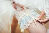 Bride putting a wedding garter on her leg — Stock Photo