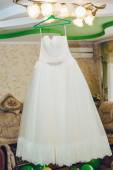 Flounces of delicate textile wedding dress hanging on luster at hotel room. — Stockfoto