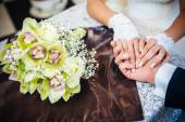 Close up hands of Loving couple sitting in a cafe on their wedding day. Bouquet flowers — Stock Photo