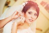 Brincos de noiva exploração. Retrato de uma mulher linda, ajustando seu brinco. Momento de preparação para o casamento. — Fotografia Stock