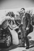 Happy groom helping his bride out of the wedding car. — Stock Photo