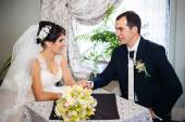 Loving couple sitting in a cafe on their wedding day. Bouquet of flowers — Stock Photo