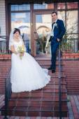 Bride and groom standing on stairs — Stock Photo