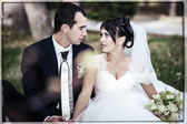 Young couple kissing in wedding gown. Bride holding bouquet of flowers — Stock Photo