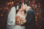 若いカップルが結婚式のガウンにキスします。花嫁持株花束 — ストック写真