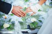 Hands of the bride and groom. wedding bouquet on black car — Stock Photo