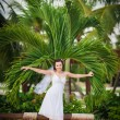 Happy nice bride walk near beach on green grass under palms. Young woman in white dress on a beach — Stock Photo #71713175