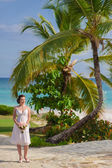 Happy nice bride walk near beach on green grass under palms. Young woman in white dress on a beach — Стоковое фото