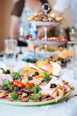 Table with food and drink. Catering table set service with silverware and glass stemware at restaurant before party — Stock Photo