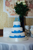 Wedding cake in white and blue combination, adorned with flowers, ribbons. — Fotografia Stock