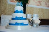 Wedding cake in white and blue combination, adorned with flowers, ribbons. — Stock Photo