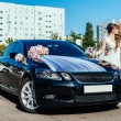 Beautiful brunette bride at white wedding with her handsome young groom in black suit stand near the car — Stock Photo #72026895