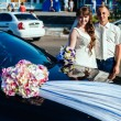 Beautiful brunette bride at white wedding with her handsome young groom in black suit stand near the car — Stock Photo #72027637