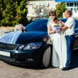 Beautiful brunette bride at white wedding with her handsome young groom in black suit stand near the car — Stock Photo #72027681