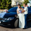Beautiful brunette bride at white wedding with her handsome young groom in black suit stand near the car — Stock Photo #72028185