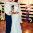 Wedding dance of young bride and groom in banqueting hall. Kiss, embrace — Stock Photo #72029113