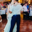 Wedding dance of young bride and groom in banqueting hall. Kiss, embrace — Stock Photo #72029149