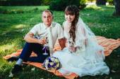 Couple just married sitting in park green grass with bouquet of flowers and wine glasses — Stock Photo