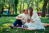Couple just married sitting in park green grass with bouquet of flowers and wine glasses — ストック写真