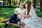 Pár si sedí v parku zelené trávě s kyticí květin a sklenice na víno — Stock fotografie