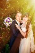 Wedding couple kissing in green summer park. bride and groom kissing, standing together outdoors, hugging among green trees. Bride holding wedding bouquet of flowers — Stock Photo