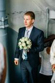 Groom holding bouquet. Concept image - young man waiting woman — Stock Photo