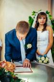 Young couple signing wedding documents. — Stock Photo