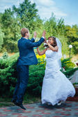 Bride and groom jumping in the air — Stock Photo