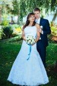 Nevěsty a ženicha na svatební den chůze venku na jarní přírody. Svatební pár, Happy novomanželský pár objímat v parku. — Stock fotografie