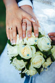 Hands of the bride and groom with rings on a beautiful wedding bouquet — Stock Photo