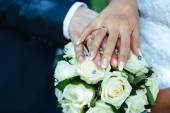新娘和新郎与上一个美丽的婚礼花束的戒指的手 — 图库照片