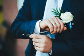 Happy Handsome caucasian groom in tuxedo thinking and putting on his bowtie. — Stock Photo