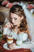 Bride in luxurious restaurant drink cup of Cappuccino or latte coffee with heart shape on her wedding. Valentines day — Stok fotoğraf