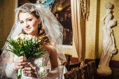 Retrato linda noiva com buquê de flores no interior de luxo no dia do casamento — Fotografia Stock