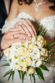 Hands with wedding rings on bridal bouquet of flowers — Stock Photo