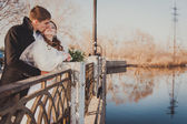 The bride and groom hugging on shore of Lake in a park. Wedding by the sea. Honeymoon. — Стоковое фото