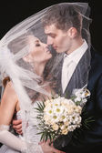 Bride And Groom Kissing Under Veil Holding Flower Bouquet In Hand. black background — Stock Photo
