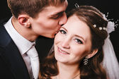 Bride and groom kissing, hugging. wedding photo taken in the studio on black background — Stockfoto
