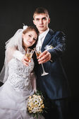 Wedding couple kissing and drinking champagne. Black background. — Stockfoto