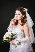 Fashion model with bridal bouquet drinking champagne and wearing wedding dress at black studio background — Stock Photo