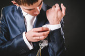 Hands of wedding groom getting ready in suit. black studio background — Stockfoto