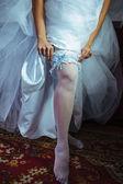 Liga en la pierna de la novia, novia sexy slim de lujo nupcial vestido mostrando su liguero seda con cinta de oro. mujer tienen preparación final para la ceremonia de la boda. Momentos del día de la boda — Foto de Stock