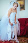 Garter on leg of bride, slim sexy bride in bridal luxury dress showing her silk garter with golden ribbon. woman have final preparation for wedding ceremony. Wedding day moments — Stock Photo