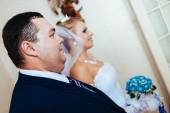 Brides hand putting the boutonniere flower on  groom — Stock Photo