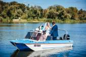 Newly married couple riding in boat on river — Stock Photo