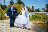 Loving wedding couple walking and kissing near water — Stock Photo