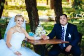 The bride and groom on their wedding day, sitting at  table with the bridal bouquet. — Stock Photo
