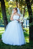 Beautiful bride posing outdoor at the park in her wedding day — Stock Photo