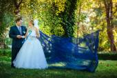 Bride and groom in the park with flying fabric. — Стоковое фото
