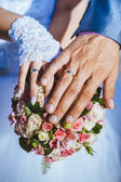 Hands of bride and groom with rings on wedding bouquet. — Stock Photo